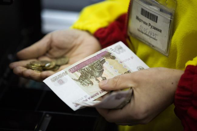 © Bloomberg. A cashier handles ruble banknotes and coins inside a Magnit PJSC hypermarket store at the Hanoi-Moscow trade centre in Moscow, Russia, on Wednesday, Feb. 28, 2018.