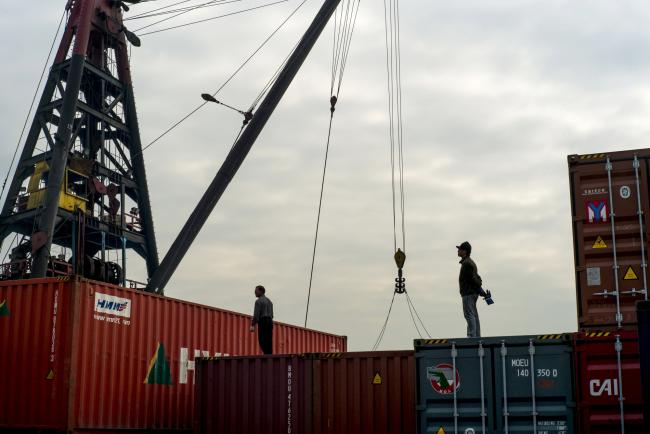 © Bloomberg. Workers stand atop shipping containers at the Kwai Tsing Container Terminals in Hong Kong, China.