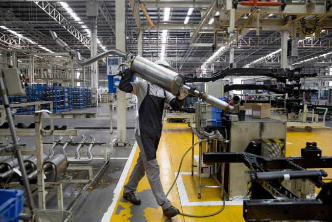 © Bloomberg. A worker prepares to install an exhaust pipe on the chassis of a Nissan Motor Co. Navara pickup truck on an assembly line at the company's plant in Samut Prakan, Thailand, on Tuesday, April 25, 2017. Nissan andMitsubishi Motors Corp.still have a small presence in Southeast Asia and the two alliance partners can target to at least double their current market share, saidCarlos Ghosn, who's chairman of both companies.