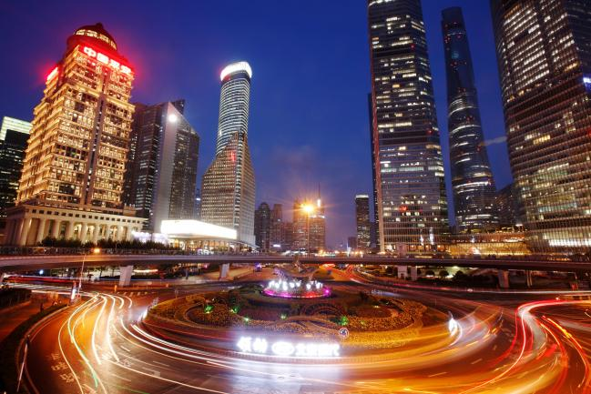 © Bloomberg. The light trails of passing traffic illuminate the road traffic roundabout on the Lujiazui ring road as skyscrapers and high rise towers stand beyond in Shanghai, China, on Monday, Aug. 22, 2016. As China's travel market takes off, all eyes should be on the country's roughly 400 million millennials, who will drive spending on airfare, hotels, theme parks, casinos and cruises.
