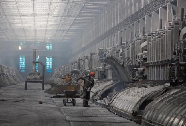 © Bloomberg. A worker uses a shovel to move material in an electrolysis bath in the electrolysis shop at the Sayanogorsk aluminium smelter, operated by United Co. Rusal, in Sayanogorsk, Russia.