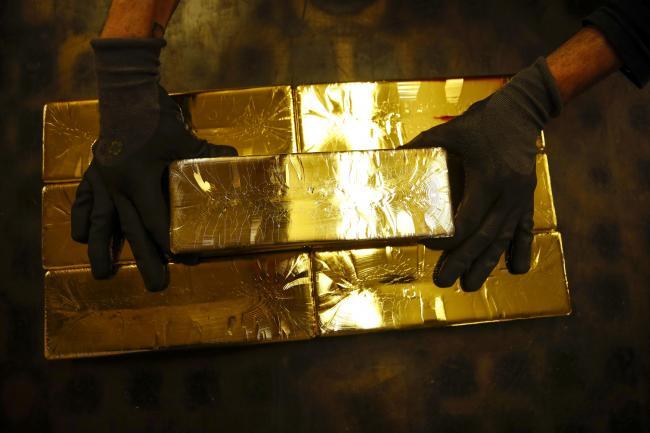 © Bloomberg. A worker stacks 12.5 kilogram gold bullion bars at the Valcambi SA precious metal refinery in Balerna, Switzerland. Photographer: Stefan Wermuth/Bloomberg