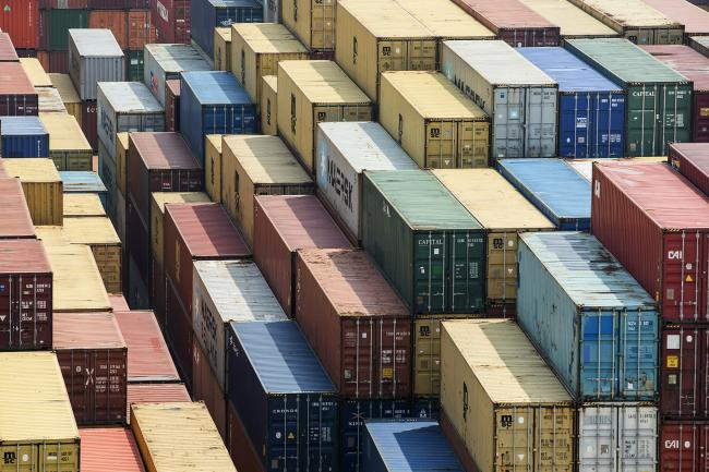 © Bloomberg. Shipping containers stand in a terminal at the Yangshan Deep Water Port in Shanghai, China, on Friday, March 23, 2018. The trade conflict between China and the U.S. escalated, with Beijing announcing its first retaliation against metals levies hours after President Donald Trump outlined fresh tariffs on $50 billion of Chinese imports and pledged there's more on the way.