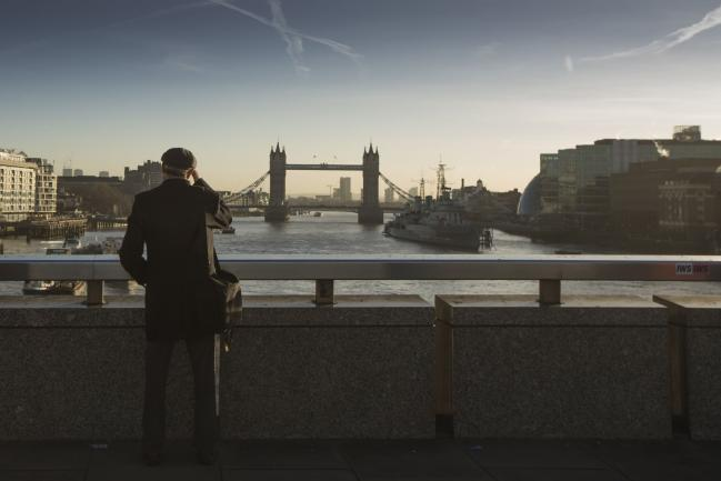 © Bloomberg. A commuter stops on London Bridge to view Tower Bridge in the distance in London, U.K., on Monday, Dec. 18, 2017. U.K. firms wanting workers face the tightest labor market in two decades. In 2011, there were almost six unemployed people for every vacancy; now there are fewer than two, the lowest ratio since records began in 2001.