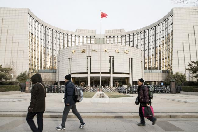 © Bloomberg. Pedestrians walk past the People's Bank of China headquarters in Beijing, China, on Monday, Jan. 7, 2019. The central bank on Friday announced another cut to the amount of cash lenders must hold as reserves in a move to release a net 800 billion yuan ($117 billion) of liquidity and offset a funding squeeze ahead of the Chinese New Year.