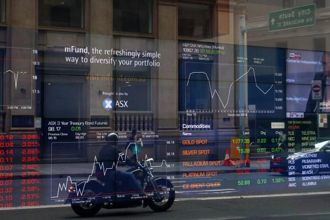 © Bloomberg. A motorcyclist is reflected in a window as electronic boards display stock information at the Australian Securities Exchange, operated by ASX Ltd., in Sydney, Australia, on Friday, Jan. 11, 2019. Australian consumer confidence slumped the most in more than three years, amid pessimism over falling property prices and economic growth, after the nation's dollar tumbled to the weakest in almost 10 years at the beginning of the month. Photographer: Lisa Maree Williams/Bloomberg
