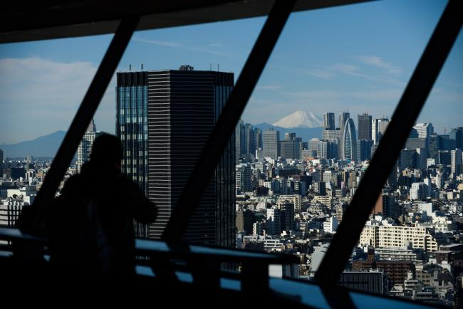 © Bloomberg. Mount Fuji stands beyond buildings as a visitor looks out at the skyline from an observation deck in Tokyo, Japan, on Friday, Jan. 11, 2019.