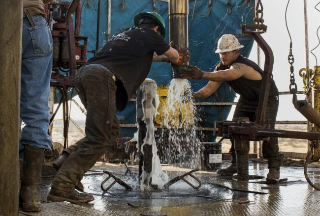 © Bloomberg. Workers connect drill bits and drill collars, used to extract natural petroleum, on Endeavor Energy Resources LP's Big Dog Drilling Rig 22 in the Permian basin outside of Midland, Texas, U.S.