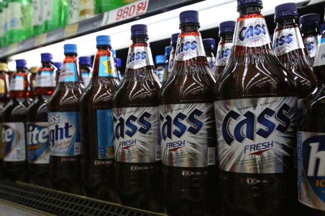 © Bloomberg. Bottles of Oriental Brewery Co. Cass Fresh beer, right, are displayed for sale at a supermarket in Incheon, South Korea.