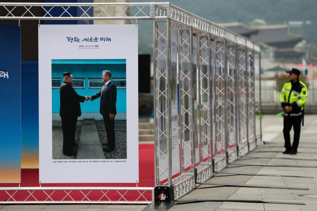 © Bloomberg. A police officer walks past a photo exhibition featuring North Korean Leader Kim Jong Un and South Korean President Moon Jae-in at Gwanghwamun Square in Seoul, South Korea, on Wednesday, Sept. 19, 2018.