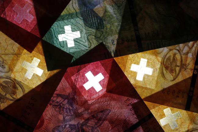 © Bloomberg. The cross of the Swiss national flag sits on Fifty, twenty and ten Swiss franc banknotes in an arranged photograph in Bern, Switzerland, on Wednesday, June 12, 2019. With the franc having touched a two-year high against the euro, SNB President Thomas Jordan and fellow policy makers are feeling the pressure from risks such as trade tensions, a German industrial slump, Italian politics and Brexit. Photographer: Stefan Wermuth/Bloomberg
