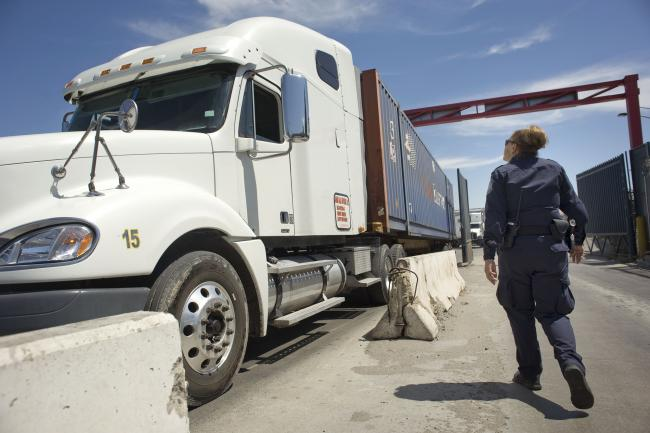 © Bloomberg. A U.S. Customs and Border Protection (CBP) officer walks next to a truck entering from Mexico at the Otay Mesa Cargo Port of Entry in San Diego, California, U.S., on May 23, 2017. The skirmish among House Ways and Means Committee Republicans over a border tax provision resurfaced during a May 24 hearing where Treasury Secretary Steven Mnuchin was testifying on the president's proposed fiscal year 2018 budget. Photographer: David Maung/Bloomberg