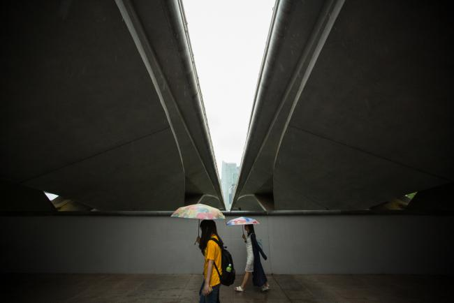 © Bloomberg. Women carrying umbrellas walk under a bridge near the Esplanade Theater in Singapore, on Wednesday, July 12, 2017. Singapore is scheduled to release second-quarter gross domestic product data on July 14.