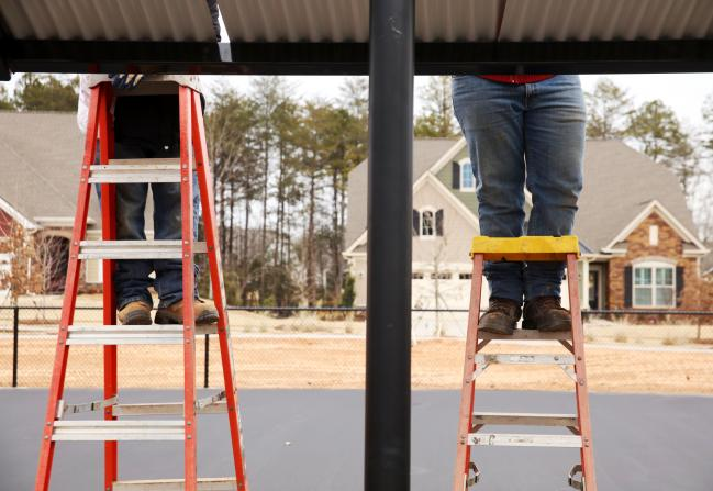 © Bloomberg. Contractors stand on ladders while working at the Lennar Corp. Tree Tops community development in Lancaster, South Carolina, U.S. Photographer: Travis Dove/Bloomberg