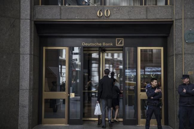 © Bloomberg. People enter Deutsche Bank AG headquarters on Wall Street in New York, U.S., on Thursday, April, 26, 2018. Deutsche Bank AG is planning to cut more than 10 percent of U.S. jobs as it withdraws from businesses where it can't compete, a person briefed on the matter said.