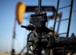 UPDATE 3-Oil edges up on ongoing supply cuts, but slowing economy drags