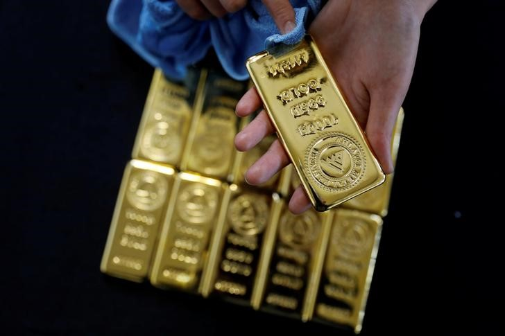 © Reuters.  Gold prices end lower for third straight week weighed down by stronger dollar