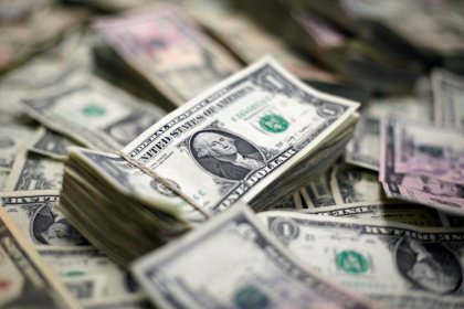 Dollar stays near a seven-month peak, but trade tensions limit gains