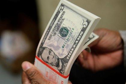 Dollar holds onto gains, but sentiment remains fragile
