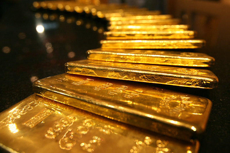 Gold prices fell while the dollar inched up