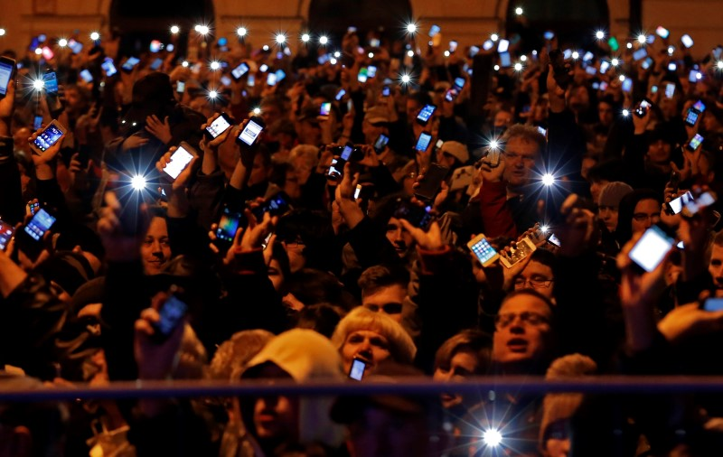© Reuters People hold up their mobile phones as they protest against a new tax on Internet data transfers in the centre of Budapest