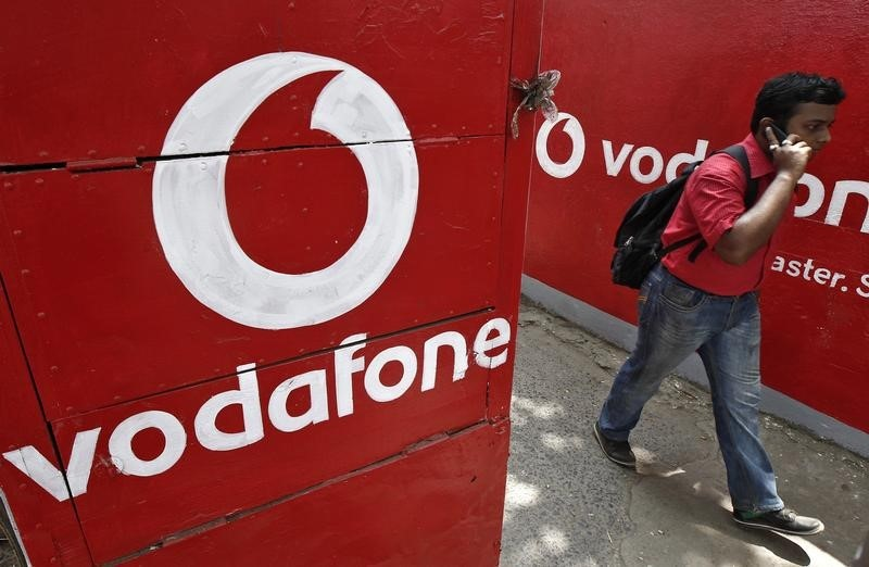 © Reuters. Man speaks on his mobile phone as he walks past the logos of Vodafone painted on a roadside wall in Kolkata
