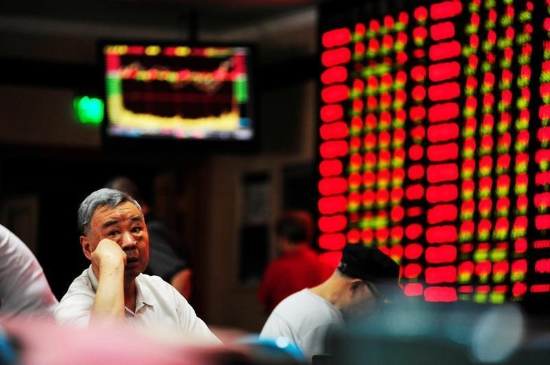 © Reuters. An investor sits in front of an electronic board showing stock information at a brokerage house in Nanjing