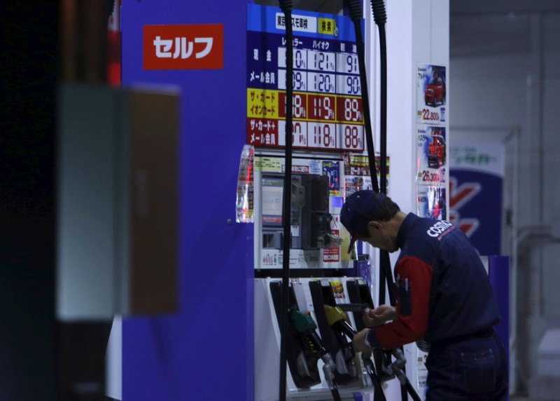 © Reuters. An employee of Cosmo Energy Holdings' Cosmo Oil service station checks its nozzles at a branch in Tokyo