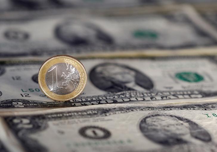 © Reuters. Купюры доллара США и монета евро
