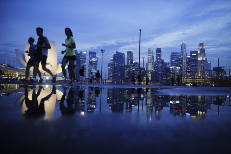 © Reuters. Joggers run past as the skyline of Singapore's financial district is seen in the background