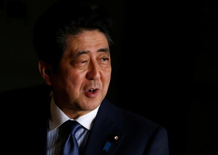 Japan's PM Shinzo Abe speaks to the media as he walks at his official residence in Tokуo