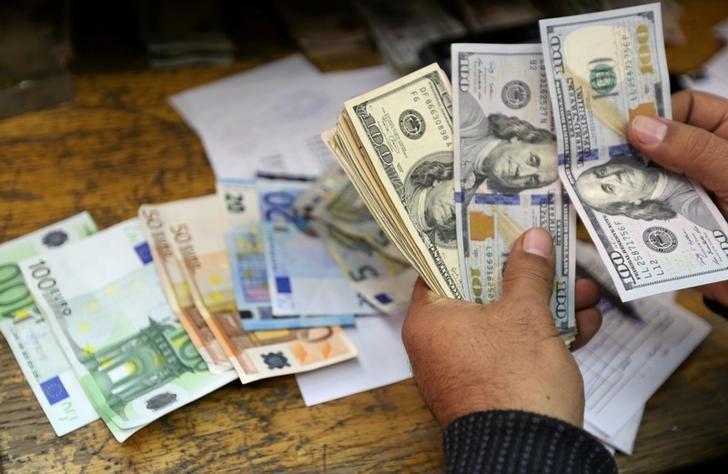 © Reuters. Сотрудник пункта обмена валют в Каире пересчитывает доллары и евро