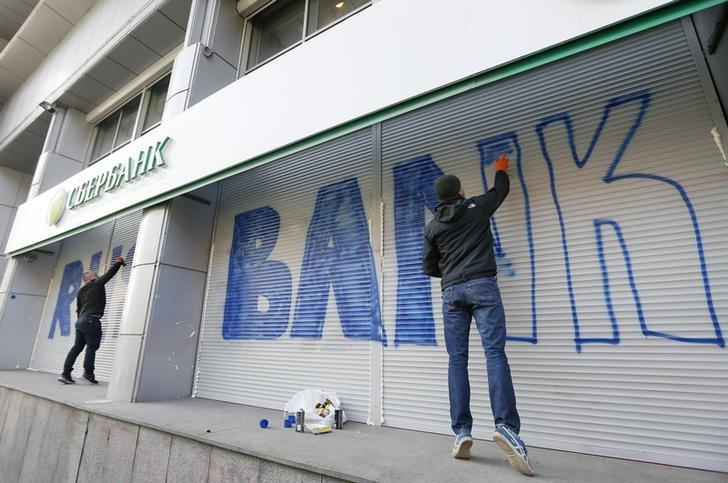 © Reuters. Люди рисуют граффити на здании отделения Сбербанка в Киеве
