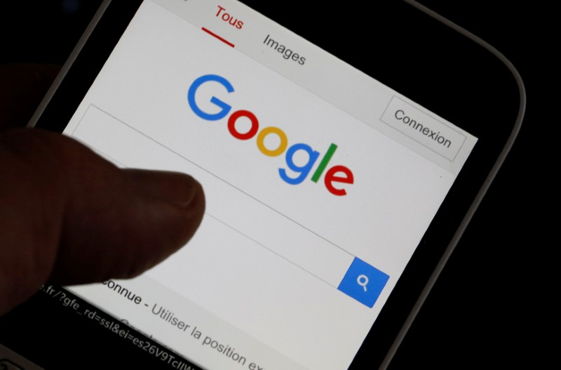 A man holds his smartphone which displaуs the Google home page, in this picture illustration taken in Bordeaux, Southwestern France
