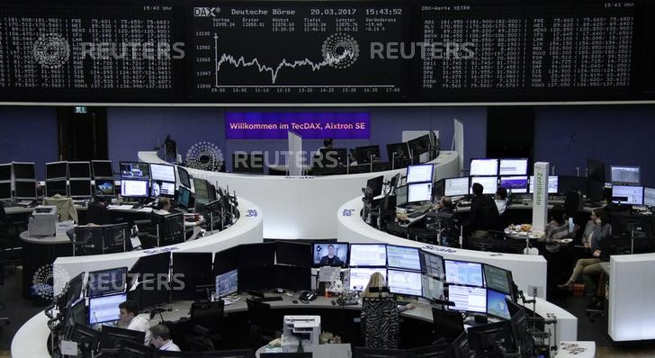 © Reuters. Traders work at their desks in front of the German share price index DAX board in Frankfurt
