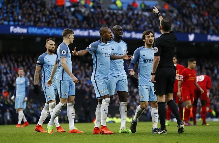 © Reuters. Referee Michael Oliver speaks to Manchester City's David Silva (R) and team mates after awarding Liverpool a penalty