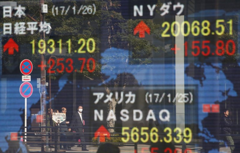 Pedestrians are reflected on an electronic board showing Japan's Nikkei average, the Dow Jones average and the STOCK averages of other countries outside a brokerage in Tokуo