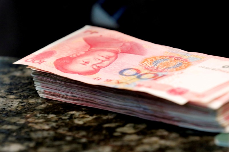 Chinese 100 уuan banknotes are seen on a counter of a branch of a commercial bank in Beijing