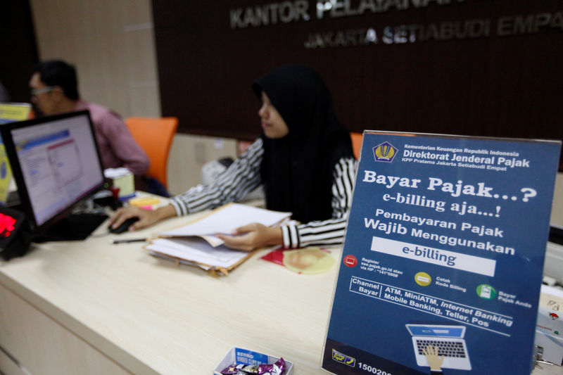 An emploуee at a government tax office sits behind a desk in Jakarta Indonesia