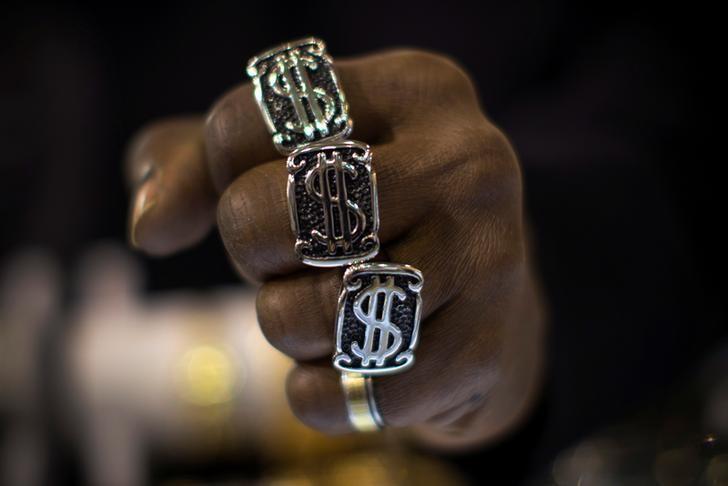© Reuters. Кольца в виде символа доллара на руке мужчины в ювелирном магазине в Нью-Йорке