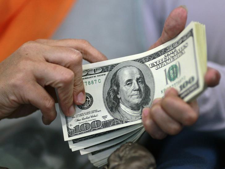© Reuters. Женщина держит в руках долларовые купюры в пункте обмена валюты в Джакарте