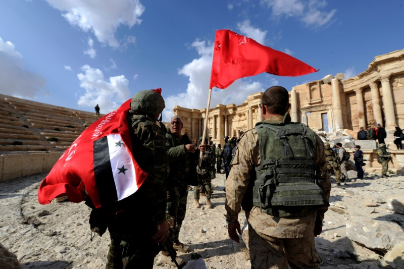 © Reuters. Syrian army soldiers carry flags in the amphitheater of the historic city of Palmyra
