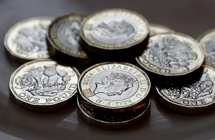 © Reuters. New one pound coins which comes into circulation today, are seen in Liverpool
