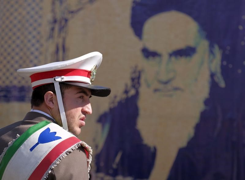 © Reuters. Iranian soldier stands guard in front of a picture of Iran's late leader Ayatollah Ruhollah Khomeini during the anniversary ceremony of Iran's Islamic Revolution in Behesht Zahra cemetery, south of Tehran