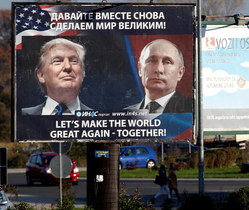 © Reuters. Pedestrians cross the street behind a billboard showing a pictures of Trump and Putin in Danilovgrad