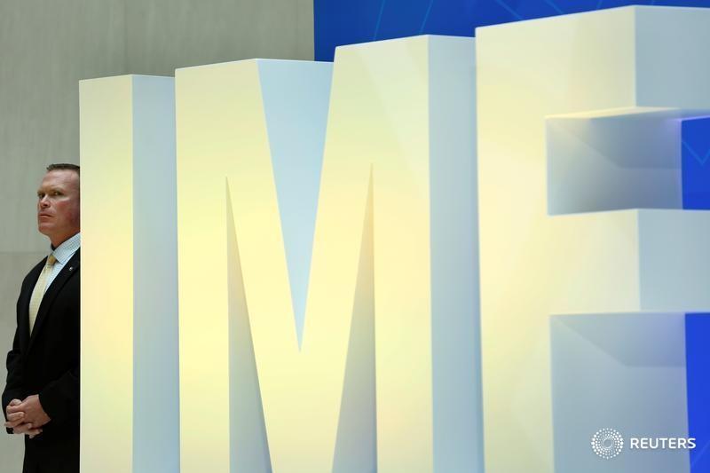 © Reuters. Охранник у логотипа МВФ в штаб-квартире фонда в Вашингтоне