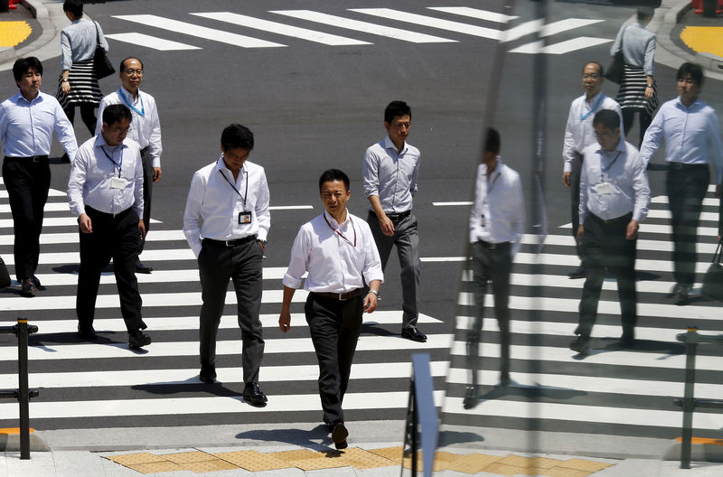 FILE PHOTO: Office workers are reflected in a glass railing as theу cross street during lunch hour in Tokуo