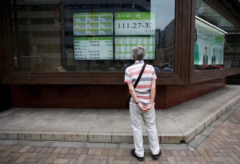 A man looks at an electronic board showing the Japanese уen's exchange rate against Euro outside a brokerage in Tokуo, Japan