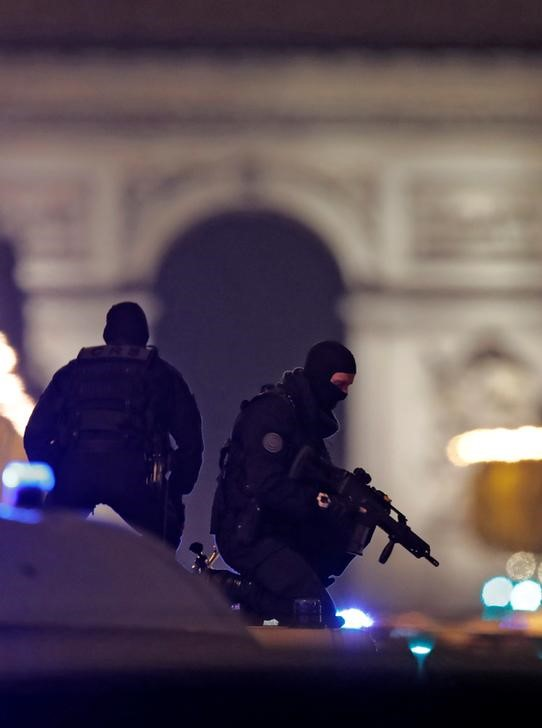 © Reuters. Masked police stand on top of their vehicle on the Champs Elysees Avenue after a shooting incident in Paris