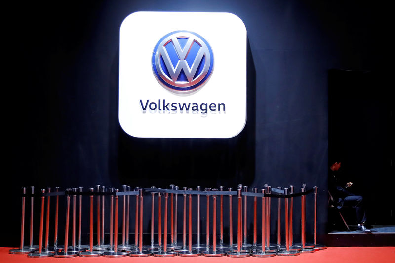 Man uses phone under VW logo at the auto show in Shanghai